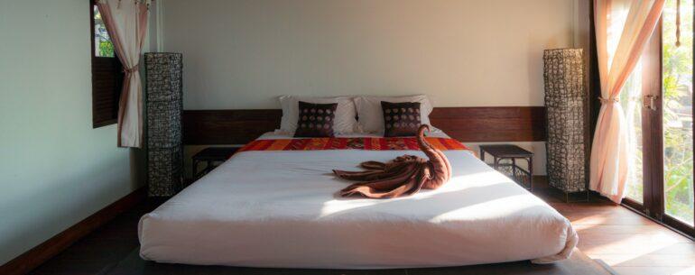 Cama grande de hotel con cisne de toallas encima de ella ejemplificando el cómo encontrar las mejores ofertas de hotel online