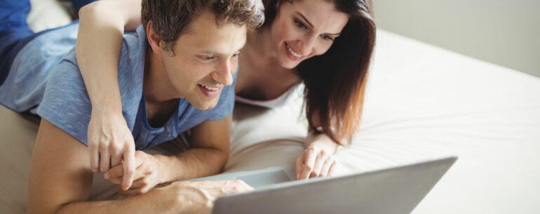 Una pareja sobre una cama revisando en su computadora Cómo obtener el mejor precio en un hotel