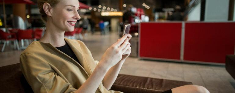 Mujer en sala de espera viendo en su celular las Mejores apps gratuitas de viaje