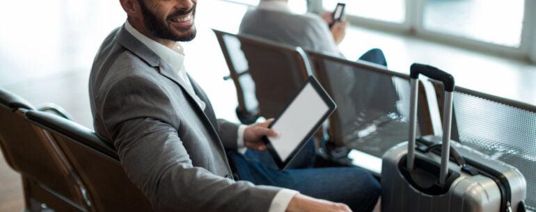 Hombre con una maleta y su smartphone en un aeropuerto ejemplificando Qué tan antes reservar un hotel para obtener el mejor precio