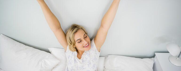 mujer levantadose en una cama de hotel (cuánta anticipación reservar un hotel para obtener el mejor precio)