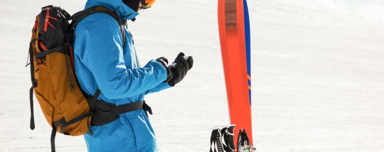 Hombre con equipo de esquí revisando en su celular la mejor aplicación para planificar un viaje