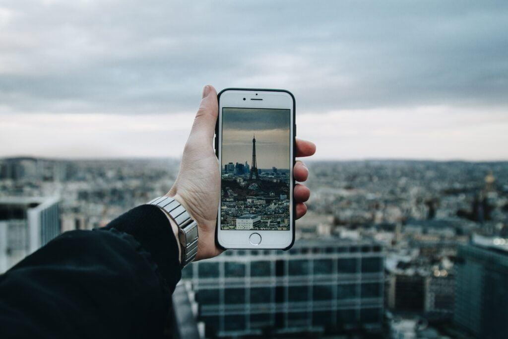 mejores aplicaciones de viaje para iPhone tomando una fotografía a la torre eiffel