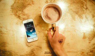 mejores apps de viaje en iPhone sobre un mapa y un mug de chocolate