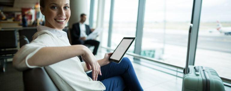 Mujer observando en su celular las mejores apps de viaje gratis