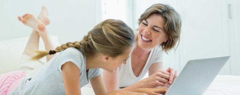 dos chicas en cama con un computador observando las mejores apps para planificar un viaje