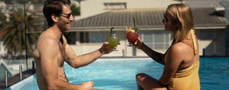 Pareja con una copa al borde de una piscina aplicando los tips para conseguir el mejor precio de hotel
