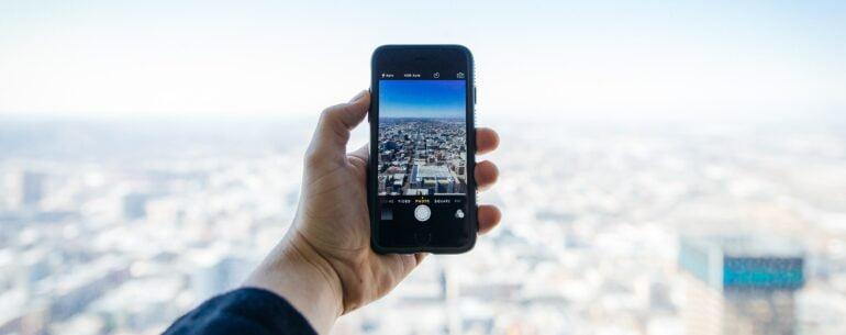 Celular en paisaje representando las Mejores apps de iPhone para viajar